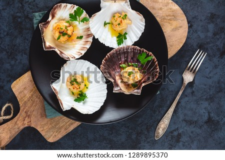 Seared scallops shell with butter, garlic and parsley.