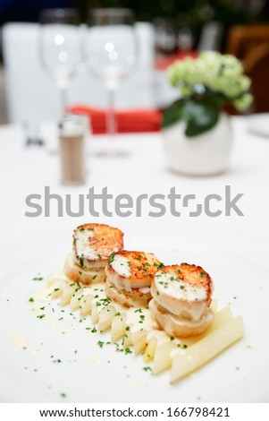 Seared scallops with white asparagus and cream sauce on restaurant table