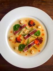 Seared yellowfin tuna with tomato consommé, px vinegar pearls, smoked paprika oil, pickled kohlrabi, nasturtium leaves
