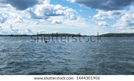 Seascape: amazing view of Baltic sea surface with two floating kayaks. Peaceful view of Archipelago at sunny summer  time. Horizon. Blue sky with white clouds. Beautiful picture of Scandinavia.