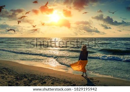 Seascape at sunrise with beautiful sky. Woman on the beach. Young happy woman in a yellow fluttering dress walks along the seashore. The girl looks at the magical sunrise. Seagulls fly over the beach