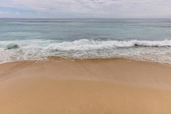 Seascape background. Sandy beach, milky foam waves, blue ocean. Scenic waterscape. Horizon line. Nature and environment concept. Daylight. Copy space. Dreamland beach, Bali, Indonesia