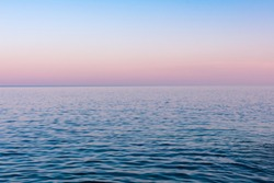 Seascape background, view from a beach on calm sea water during a beautiful pink and orange colored sunset, Vis island, travel Croatia