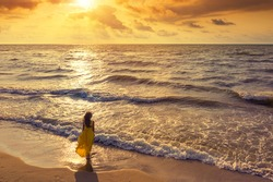 Seascape during golden sunrise with beautiful sky. Woman on the beach. Young happy woman in a yellow fluttering dress walks along seashore. The girl looks at the magical sunrise.  Above view. Top view