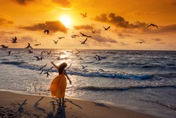 Seascape during sunrise with beautiful sky. Woman on the beach, summertime. Young happy woman with hands in the air walks on the seaside in orange dress. Seagulls flying on the beach.