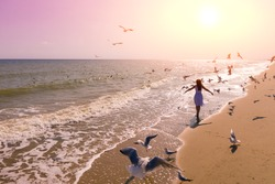 Seascape during sunrise with beautiful sky. Woman on the beach, summertime. Young happy woman with hands in the air walks on the seaside in dress. Seagulls flying on the beach.