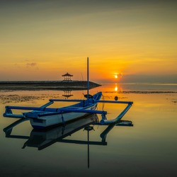 Seascape. Fisherman boat jukung. Sunrise landscape. Gazebos on an artificial island in the ocean. Water reflection. Sun on horizon. Slow shutter speed. Soft focus. Sanur beach, Bali, Indonesia.
