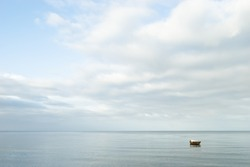 Seascape. Lonely boat on a quiet sea surface