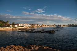 Seascape of a calm Mediterranean sea with the sun illuminating the houses of the town of Cabo de Palos, Murcia, Spain