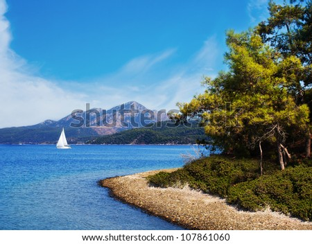 Seascape of Aegean Sea with a shore and a yacht over the mountains on it, Turkey