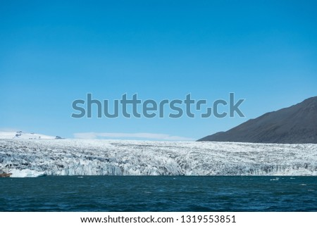 Stock Photo Seascape of Iceland with icebergs, ocean, beach, land, and snow covered mountains in the background.