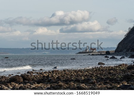 Seascape of rocky shoreline, pacific ocean and distant lighthouse at Fort Worden State Park in Port Townsend, Washington Stockfoto ©