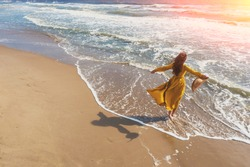 Seascape on a sunny day in summer. Woman on the beach, summertime. Young happy woman with hands in the air walks carefree on the seaside in yellow fluttering dress. View from above