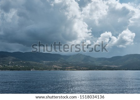 Seascape panorama from little boat in a cloudy day along the shoreline in sardinia