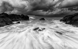 seascape rock beach,in black and white during storms , A slow shutter speed was used to see the movement ( Soft focus due to long exposure shot )