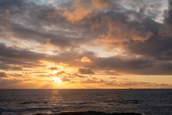 Seascape sunset, dark ocean, with sun hidden by yellow clouds, mix of other colors. Bright yellow sun rays reaching the ocean, yellow, orange, grey, and white clouds.
