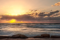 seascape sunset with cloudy sky and high surf golden hour