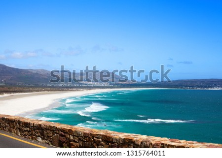 Seascape, turquoise ocean water waves, blue sky, white sand lonely beach panorama, bright sun, azure sea shore, summer vacation concept, Chapmans Peak Drive road landscape, South Africa coast travel