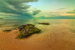 Seascape view of a calm sea with rocks with moss. Beauty sky with clouds at the horizon.