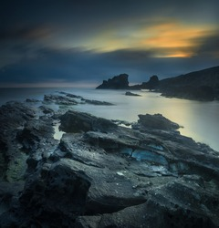 Seascape with attractive rock formations captured in the sunrise light. Long exposure photography.