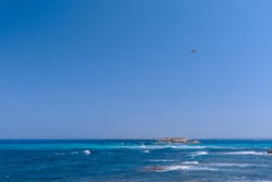 Seascape with beautiful blue sea and white waves in the distance lighthouse, seaplane in the air flies to the island of Formentera. Ibiza. Balearic Islands, Spain