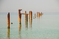 Seascape with blue calm water and rows of Rusty pipes with green algae on summer day. Rusty pipes remaining from old pier. Perspective leading to horizon, no people. Calm water.