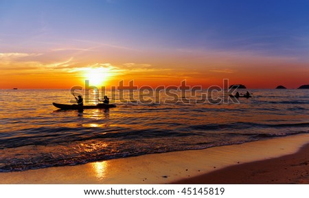 Seascape with kayakers at sunset, Chang island, Thailand