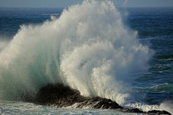 Seascape with large breaking wave and water spray