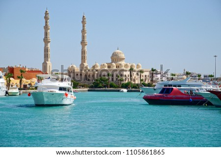 Seascape with motor yachts in marina. View of mosque  in the  background. Hurghada, Egypt #1105861865