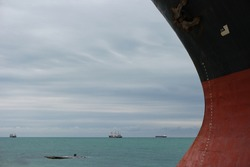 Seascape with rusty bow of large ship with draft scale numbering, large dry-cargo ships in the background