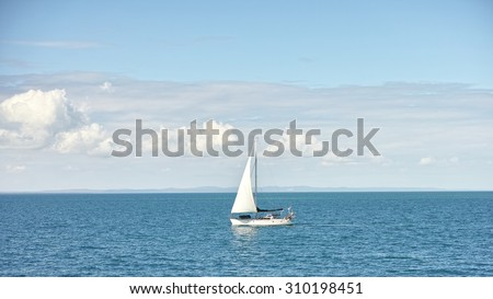 Seascape with sailboat the background of the blue sky and white clouds.