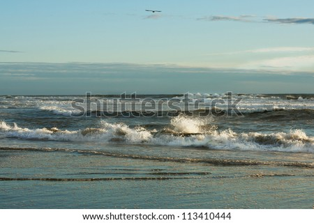 seascape with sea foam and splashing waves with blue sky and clouds