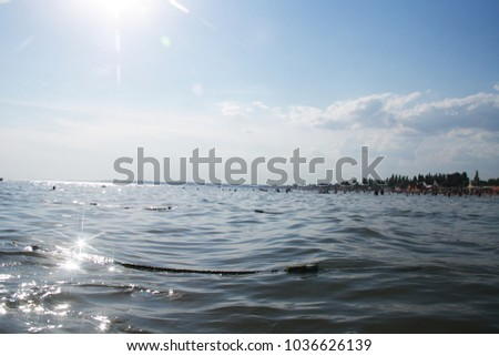 Seascape with swimming peoples and sparkling reflections from waves and cross-shaped flares #1036626139
