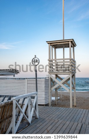 Seascape with white wood lifeguard tower. Coastal landscape with nobody. Bike parking sign made from cutout plywood. Retro style lifeguard hut on blue sky background. Summer travel idyllic scenery #1399639844