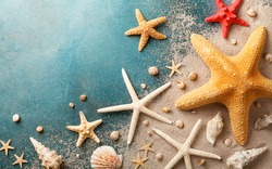 Seashell, starfish and beach sand on blue background. Summer holiday concept. Top view and flat lay.