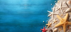 Seashell, starfish and beach sand on blue wooden background. Summer holiday banner. Top view.