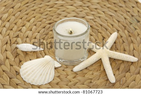 seashell with starshell and candle on woven wicker mat