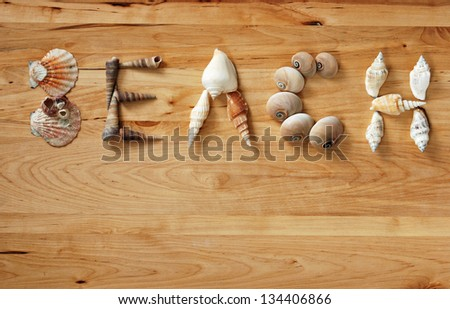 Seashells arranged to spell the word 'BEACH' on wood background with copy space.
