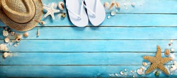 seashells on  blue wooden plank with straw hat and flip-flop -  summer holiday background