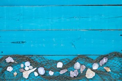 Seashells with fish net border on antique rustic teal blue wood background; blank beach sign with painted wooden copy space