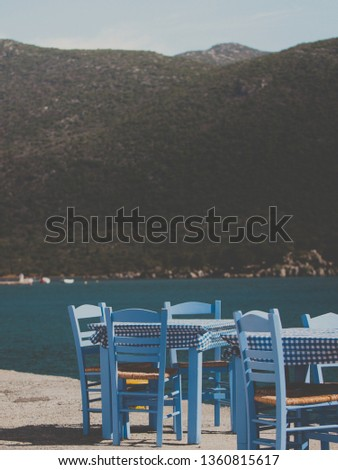 Seaside blue table and chairs open cafe outdoor restaurant in Greece on sea shore. Summer vacation on resort. #1360815617