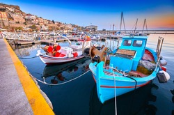 Seaside city of Kavala in Greece. Coloful evening scene, eastern Macedonia, Europe. Greek fishing boats. View on dock for boats and yachts in a beautiful spring evening.