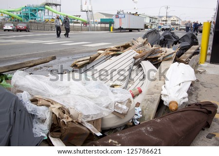 SEASIDE HEIGHTS, NJ - JAN 13: Beach umbrellas and debris on the sidewalk along Ocean Terr on January 13, 2013 in Seaside Heights, NJ. Clean up continues after Hurricane Sandy hit in October 2012. - stock photo