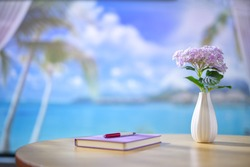 Seaside house interior wooden desk with notebook, pen, and a vase of purple flowers. Beautiful blurry view of beach landscape with blue sky and white clouds. Copy space.