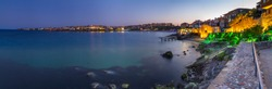 Seaside landscape, panorama, banner - view of the embankment with fortress wall during sunset in the city of Sozopol on the Black Sea coast in Bulgaria