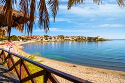 Seaside landscape - view from the cafe to the sandy beach with umbrellas and sun loungers in the town of Sozopol on the Black Sea coast in Bulgaria