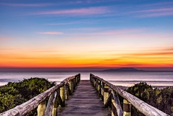 Seaside scenery in front of the sea at blue hour, sunrise, with wooden walkway, calm sea and island on the horizon line, with blue and golden sky