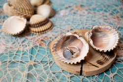 Seaside seashell with blue shine ring. Shine blue jewelry in a seashell, on a fishnet. Blue beach, fishnet and wood background. Sea shell on wooden pad. Beautiful shiny ring with blue ocean stone.