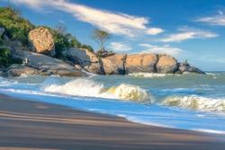 Seaside view with waves and sandy beach at Sai Noi beach, Prachuap Khiri Khan province in Thailand.