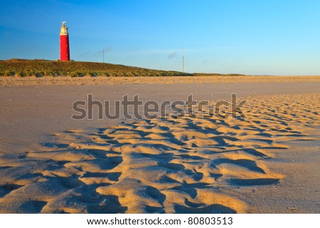 Seaside with sand dunes and lighthouse with colorful sky at sunset